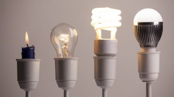 innovation: candle, tungsten bulb, two modern light bulbs