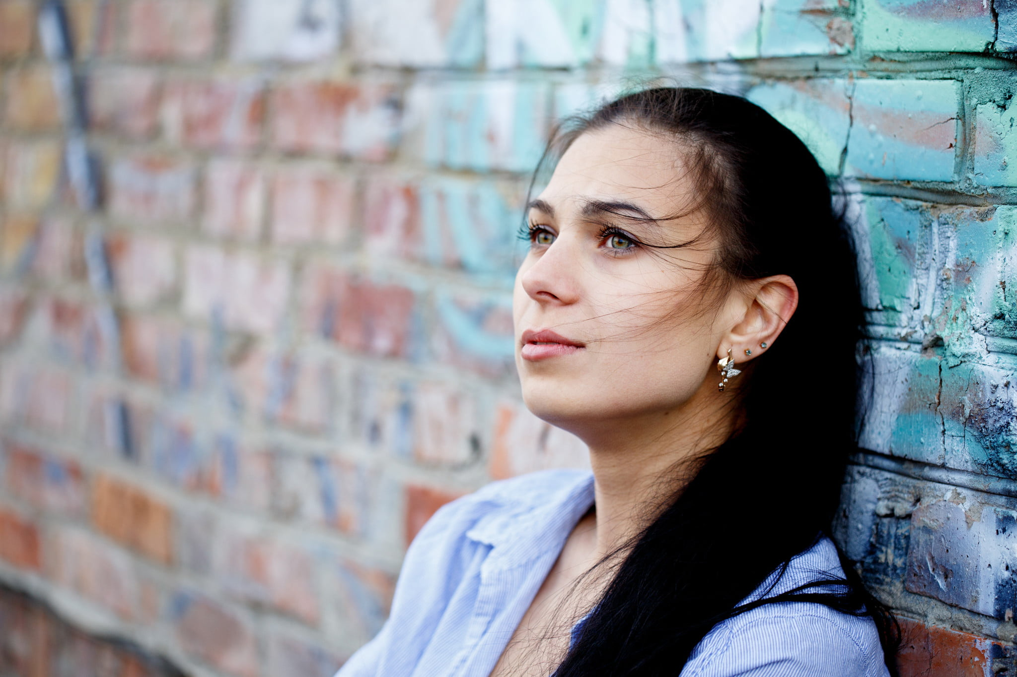 woman leans on brick wall