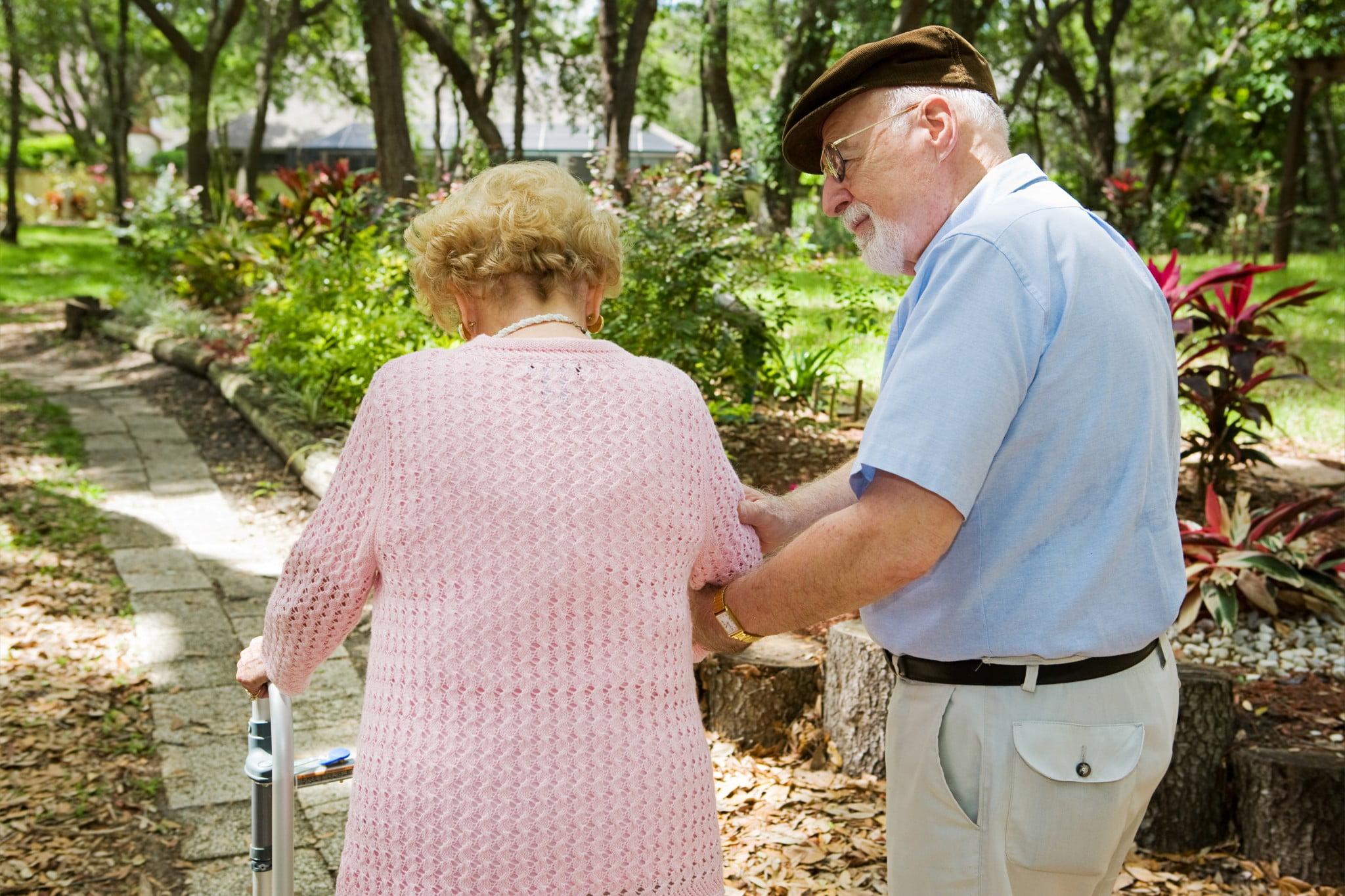 osteoporosis: frail older woman helped along by older man