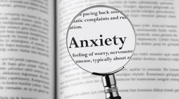 "magnifying glass over the word ""anxiety"""