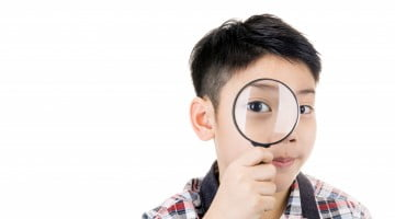 Myopia: little boy looks through magnifying glass