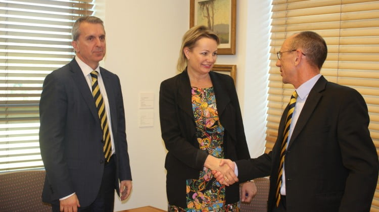 Pharmacy Guild's David Quilty shakes hands with Sussan Ley following signing of Sixth Community Pharmacy Agreement, George Tambassis in background
