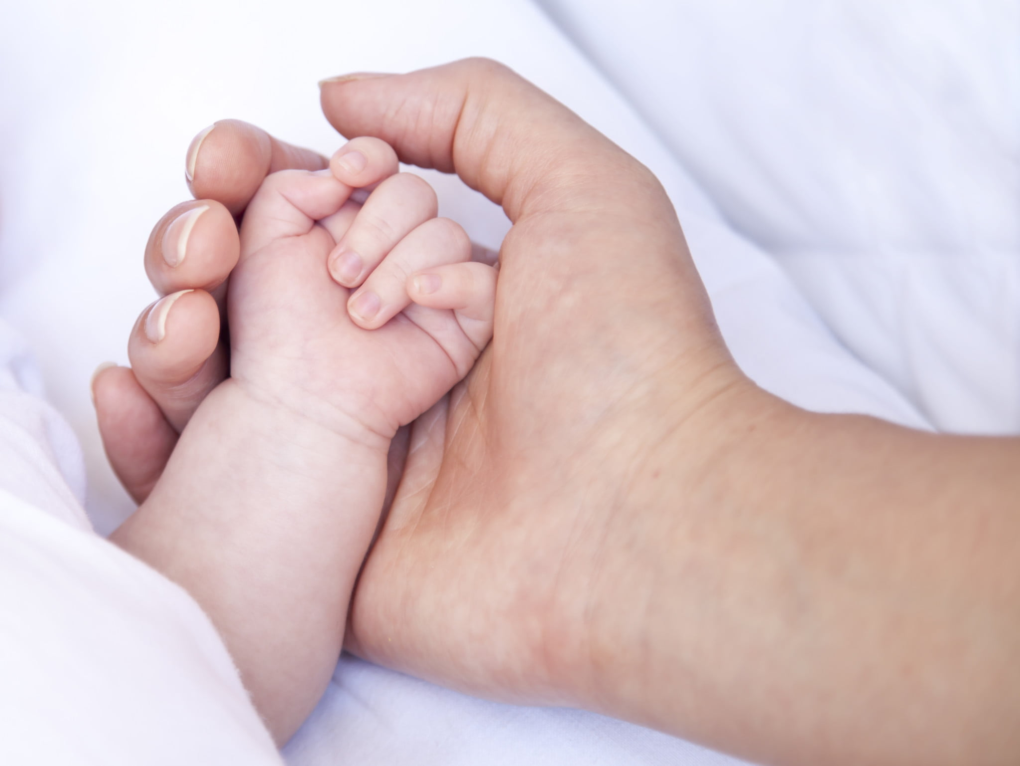 maternal deaths story: mother's hand holds baby's hand
