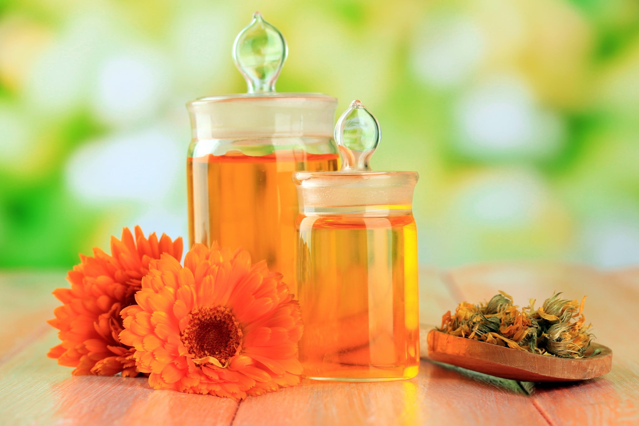 homeopathic products - jars of orange liquid and some flowers