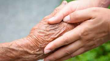 dementia-friendly communities: older hand held by younger hands