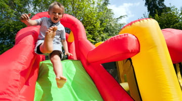 Heart Foundation: little boy sliding down bouncy castle ramp
