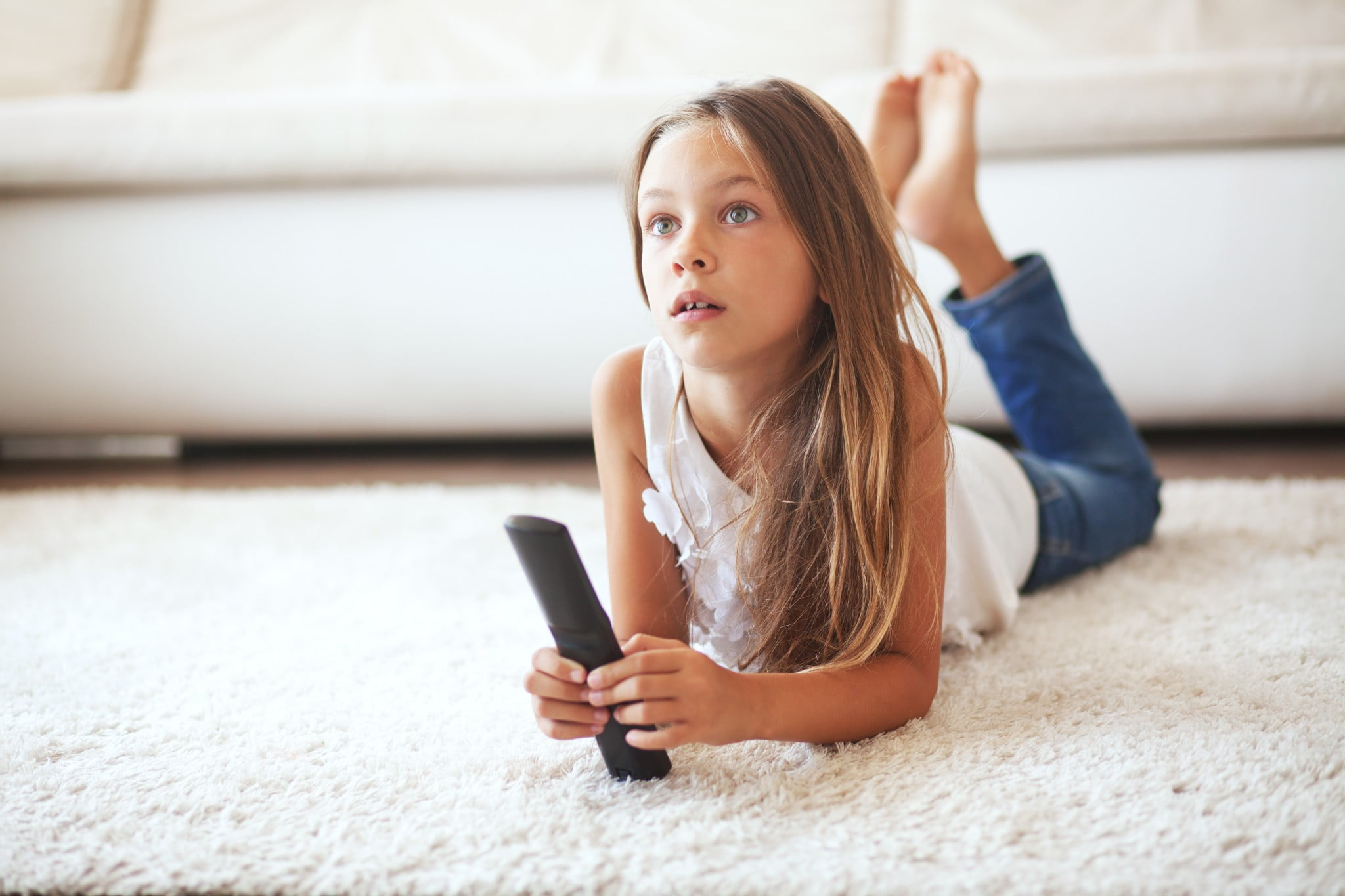 childhood inactivity: little girl lies on the floor watching tv