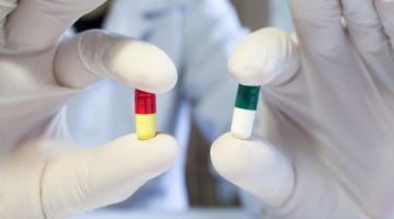 new antibiotics: gloved hands holding two antibiotic capsules
