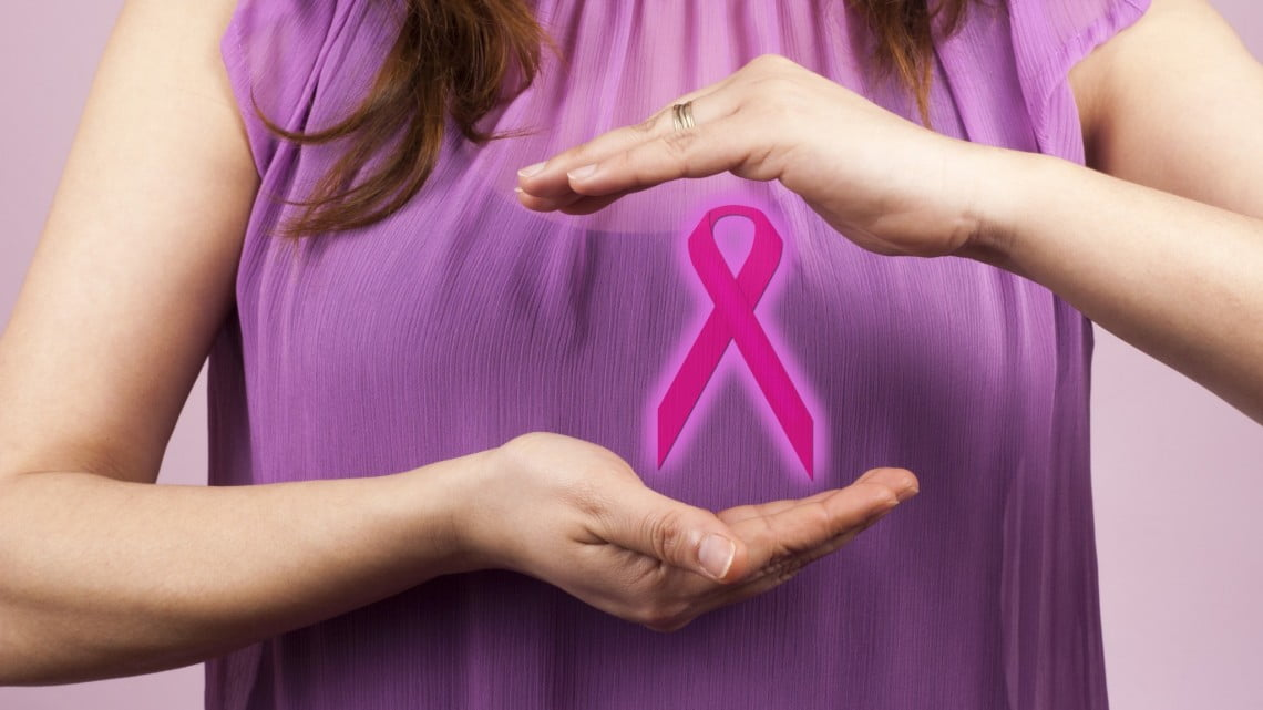 BreastScreen: woman in pink top holds pink ribbon