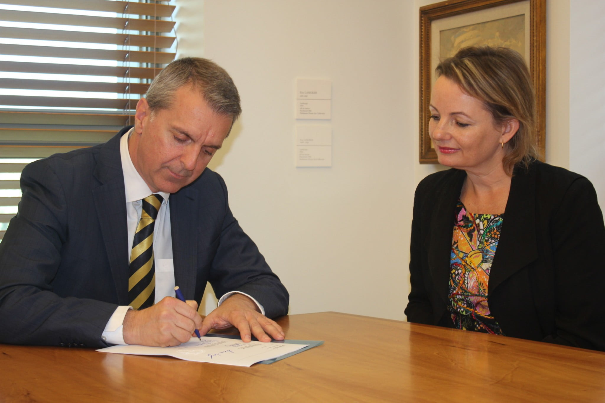 George Tambassis from the Pharmacy Guild signs the Sixth Community Pharmacy Agreement as Health Minister Sussan Ley looks on