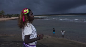 Young Aboriginal girl with bright flower in her hair looking out towards the ocean