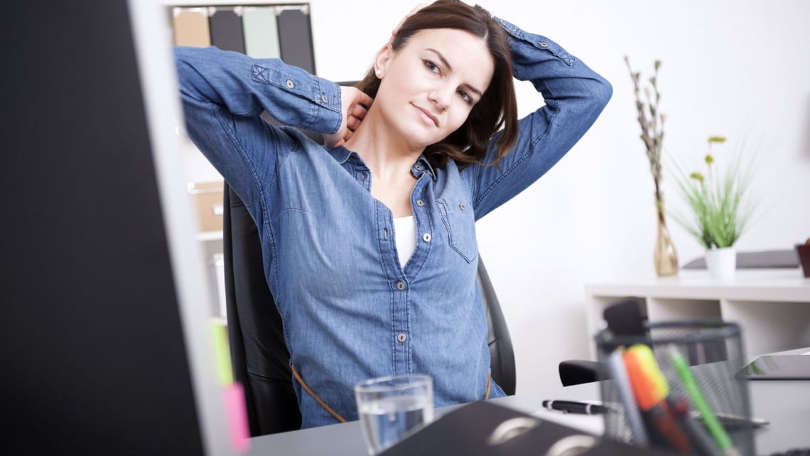 chronic pain: woman with back pain at desk