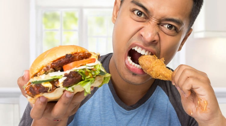 young man binge-eating a burger and drumstick