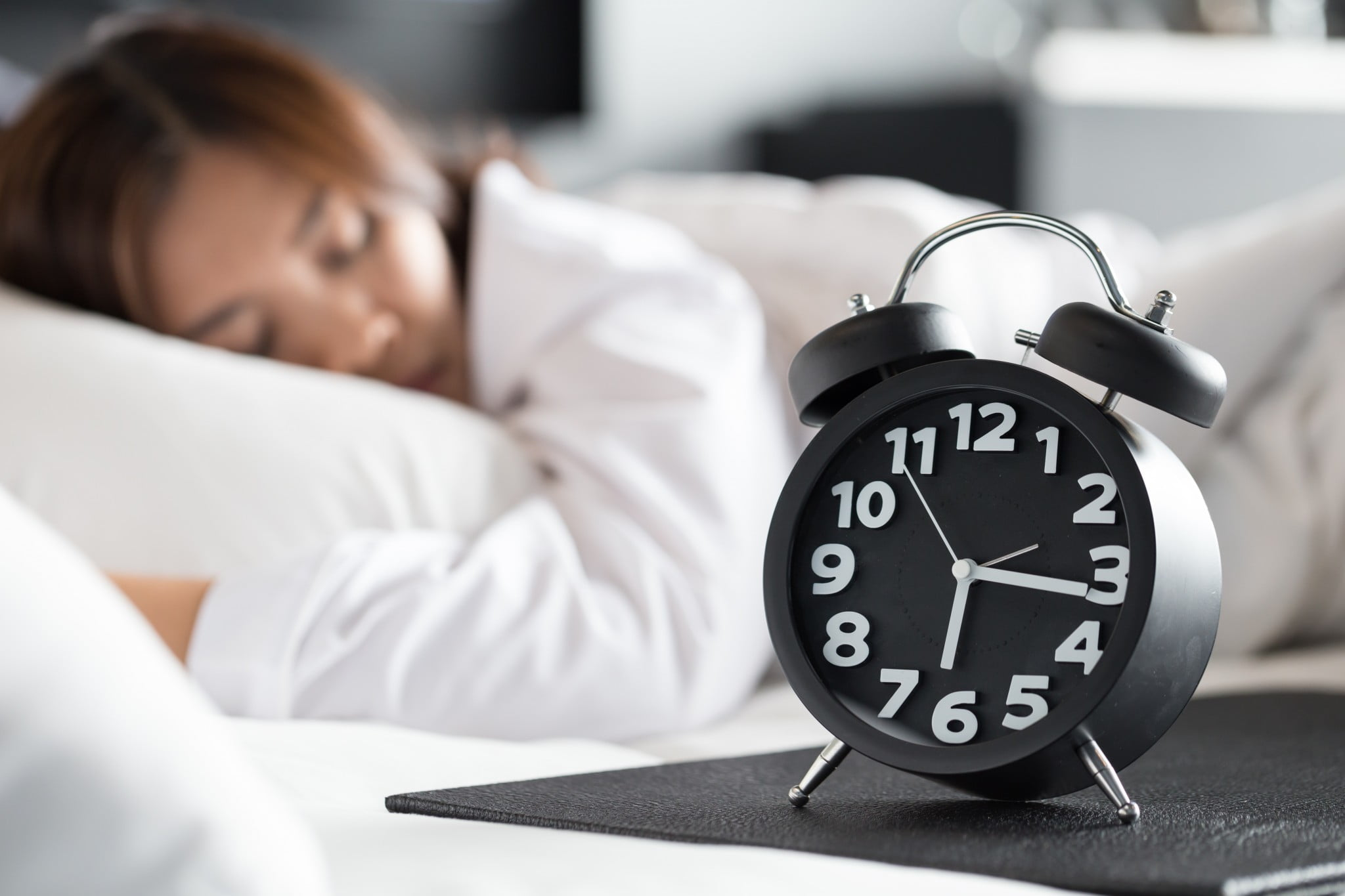 woman sleeping with alarm clock in foreground
