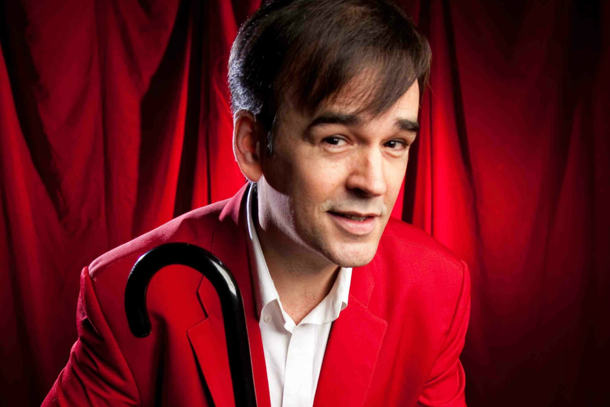 Tim Ferguson wearing red and holding cane