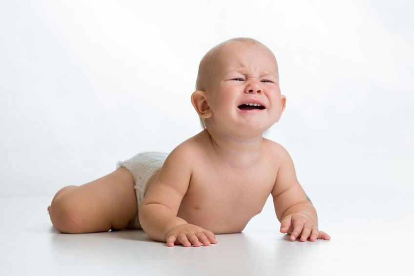 sad baby with nappy rash wearing diaper