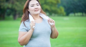 obese woman exercising in the park