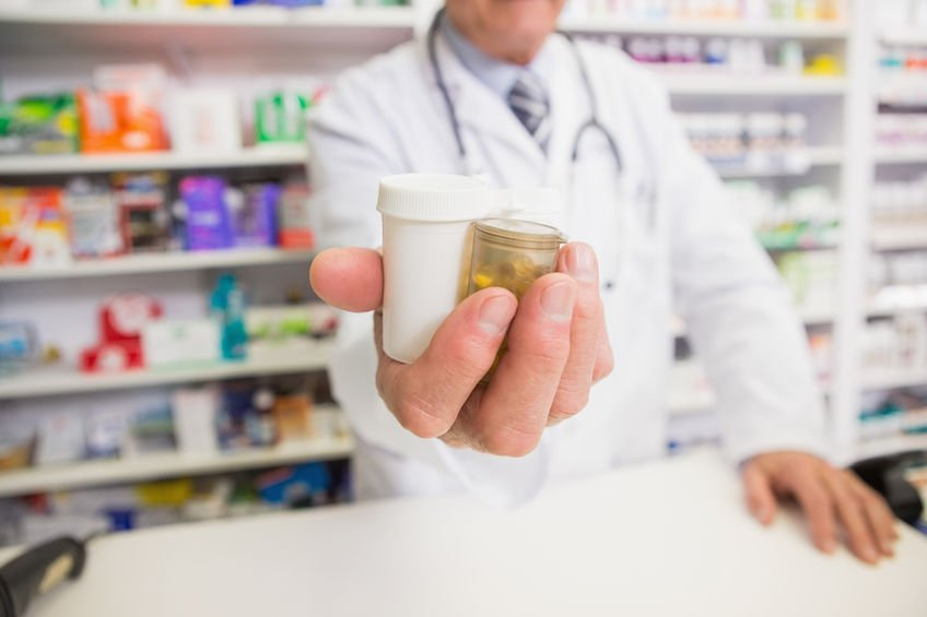 Schedule 3 - pharmacist holding out pill bottles