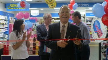 Terry White cuts the ribbon at Terry White Chemists Hilton