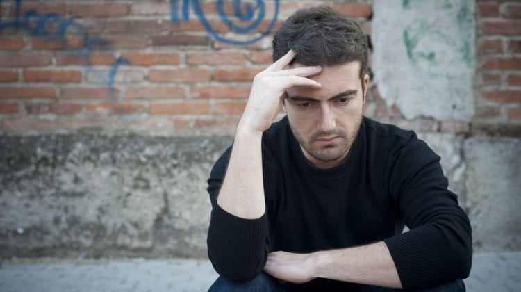 sad man in front of graffitied wall: harm minimisation story