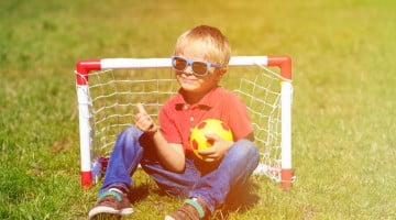 little boy playing mini soccer