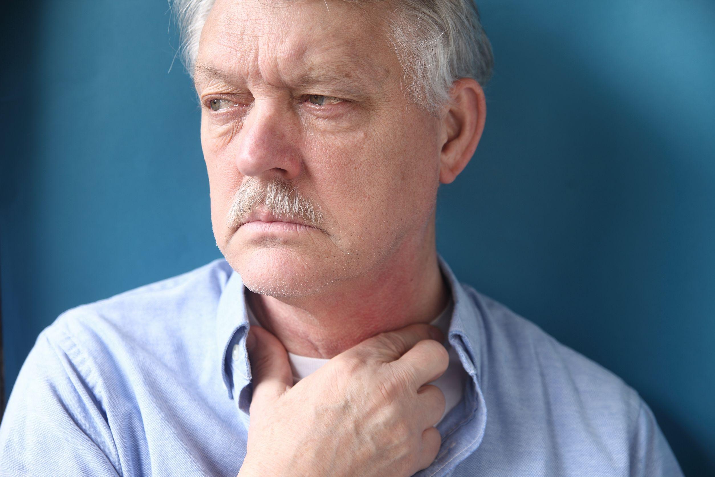 sad senior man with throat irritation