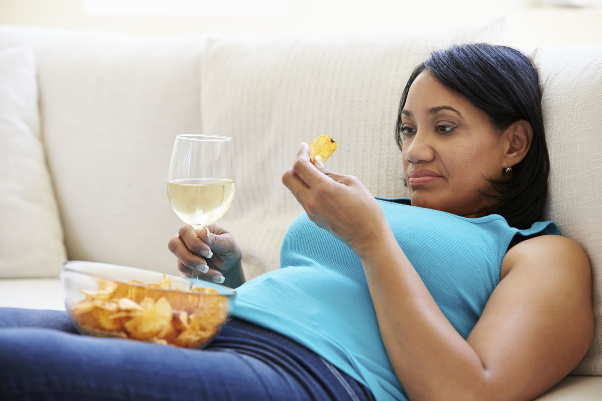 woman eating chips and drinking wine