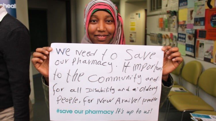 concerned cohealth Collingwood patient holds up sign in support of the pharmacy