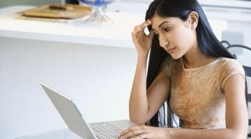 worried looking woman using laptop