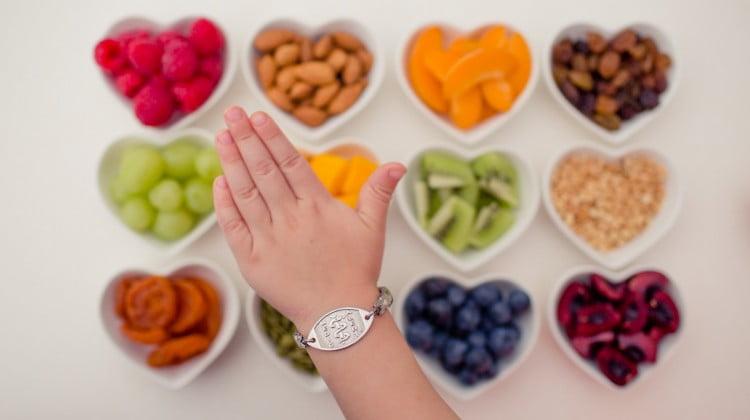 MedicAlert bracelet on wrist on background of food in heart shaped bowls