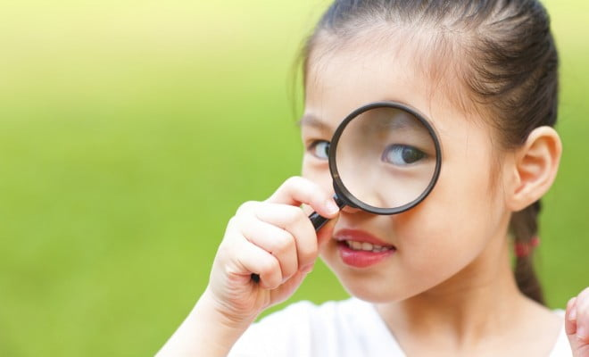 short-sighted girl holds magnifying glass up to eye