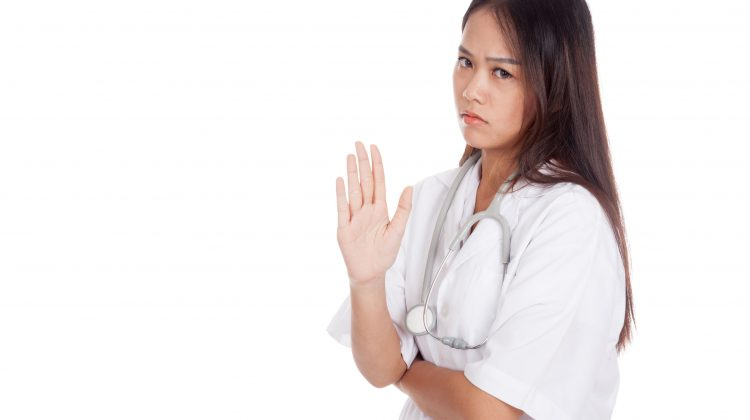 """young pharmacist or doctor with """"talk to the hand"""" body language"""