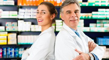 0016562 - two pharmacists standing in pharmacy or drugstore in front of shelves with pharmaceuticals