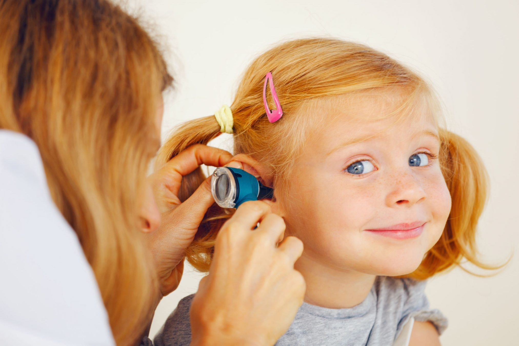 health professional checking out little girl's ear