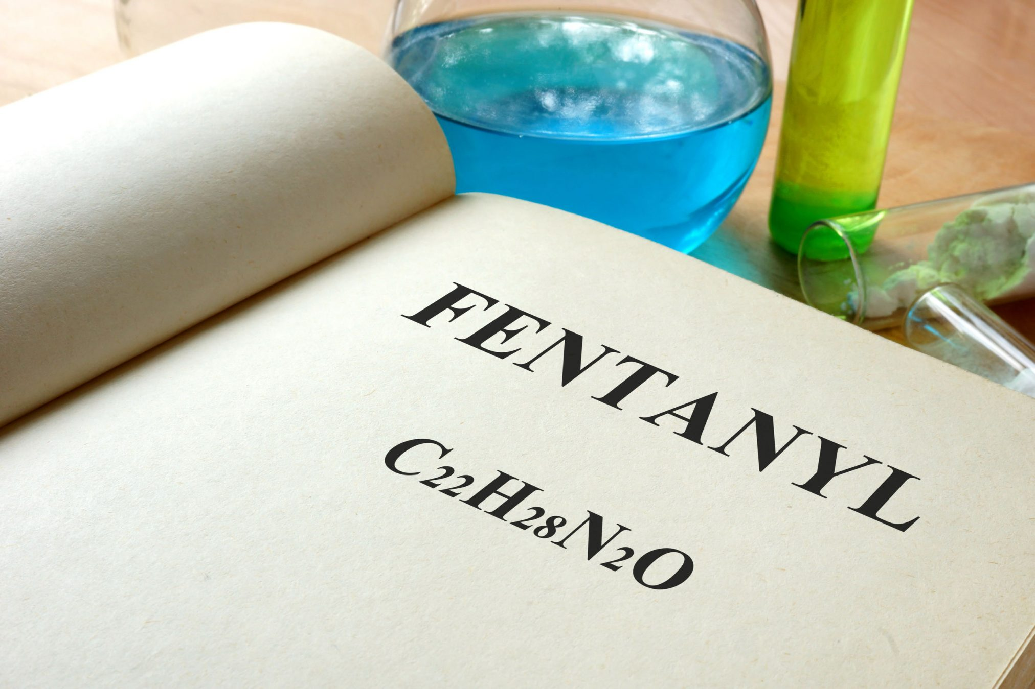 44171081 - book with fentanyl and test tubes on a table.