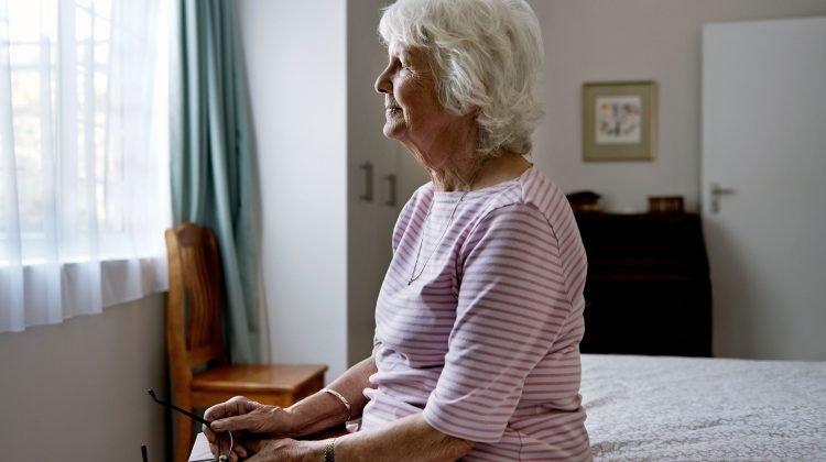 older woman sits on bed