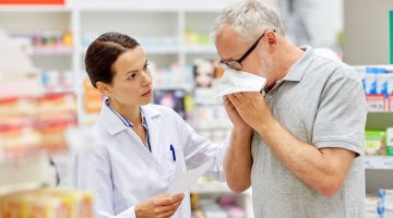 pharmacist with customer blowing his nose