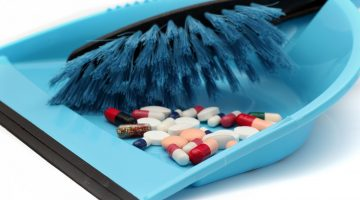 pills in brush and dustpan