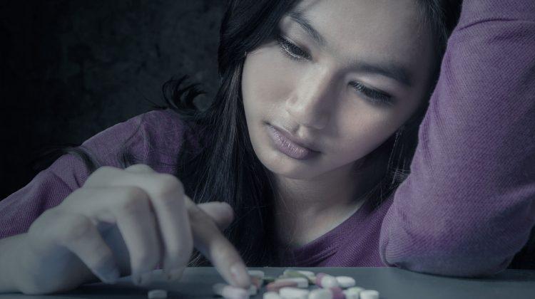 sad woman with pills