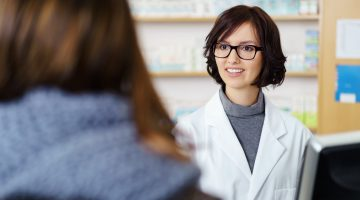 48653728 - young female pharmacist talking to a customer at the counter pleasantly.