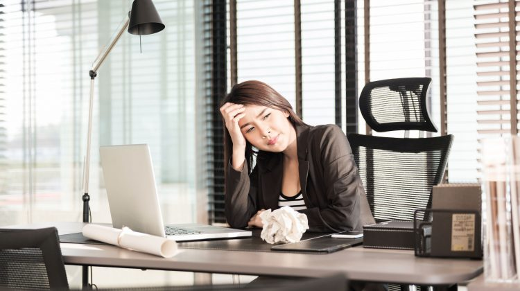 39343207 - tired and sleepy young business woman at the desk with a laptop