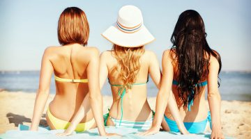 three girls on beach, only one has hat