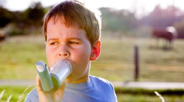 boy using inhaler and spacer