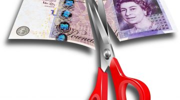 British pound being cut with scissors