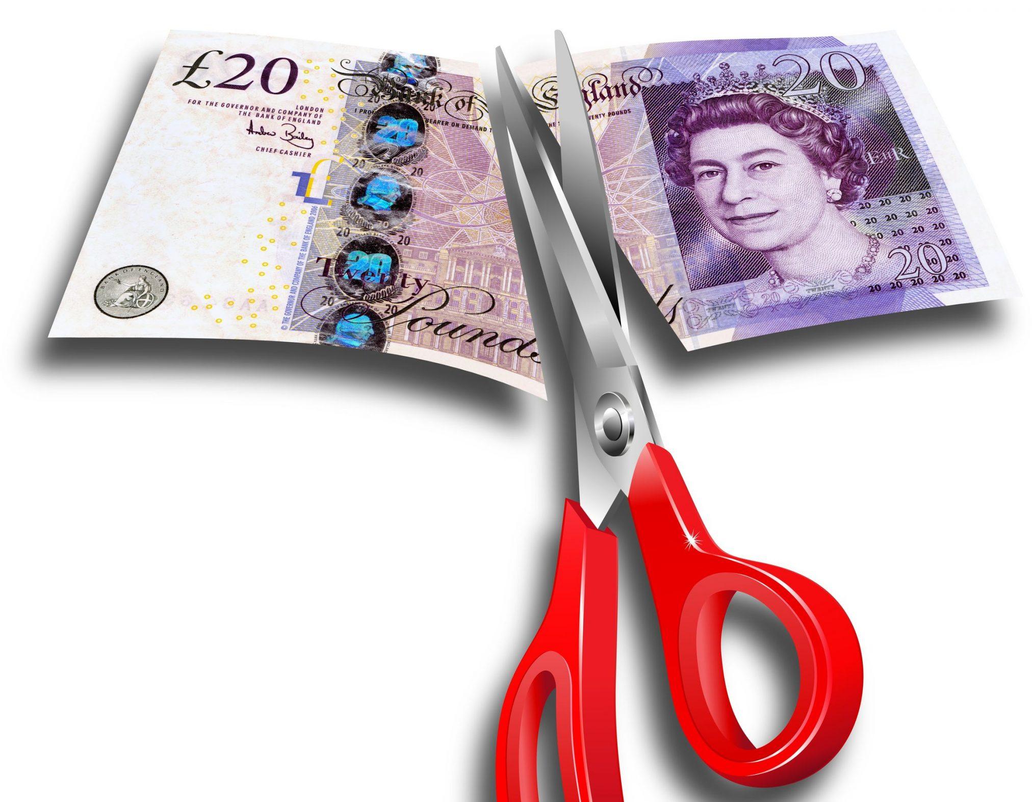 British pound being cut with scissors