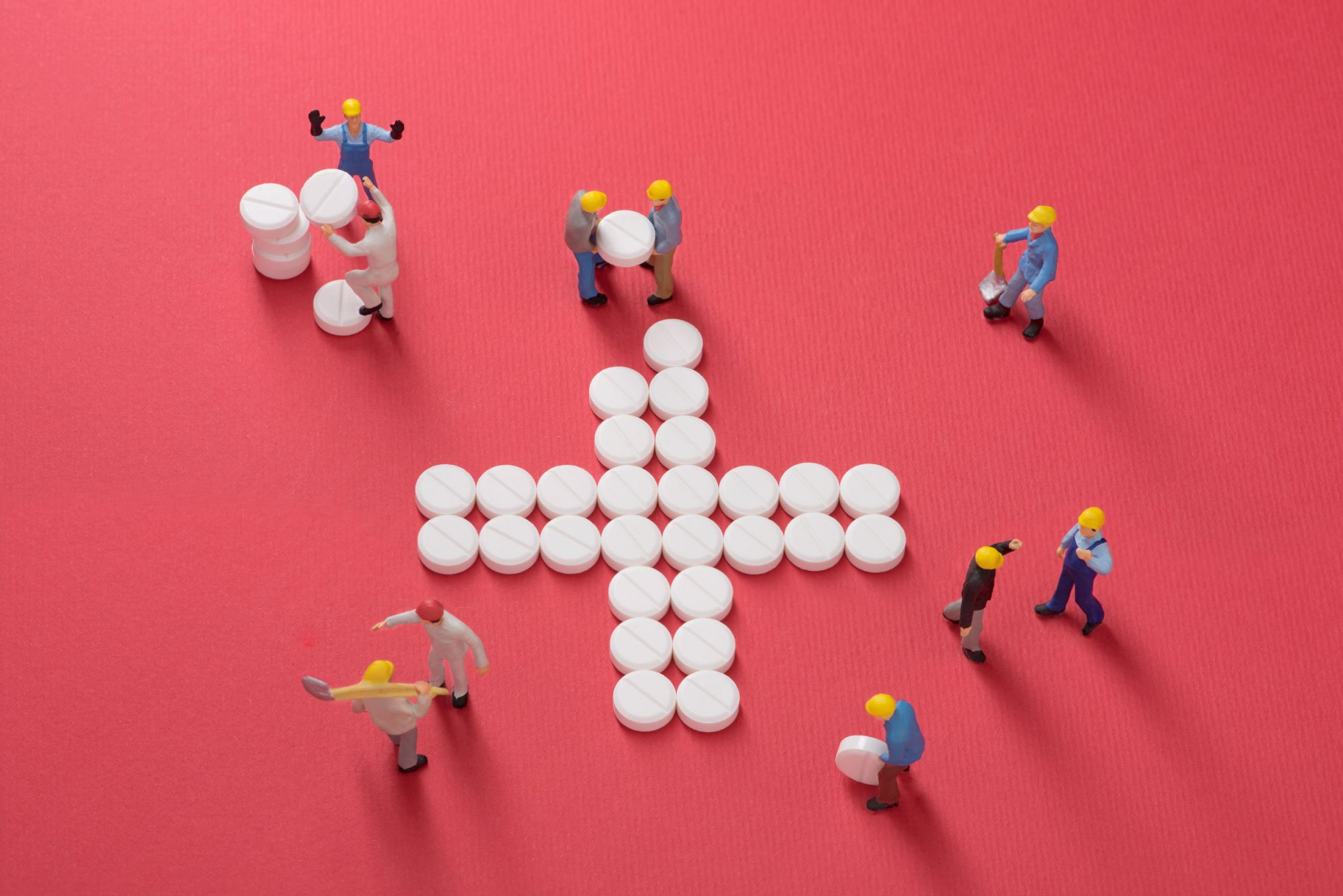workmen with pills arranged in a cross