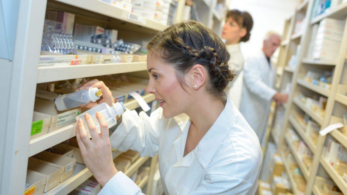 Pharmacist choosing stock from shelves