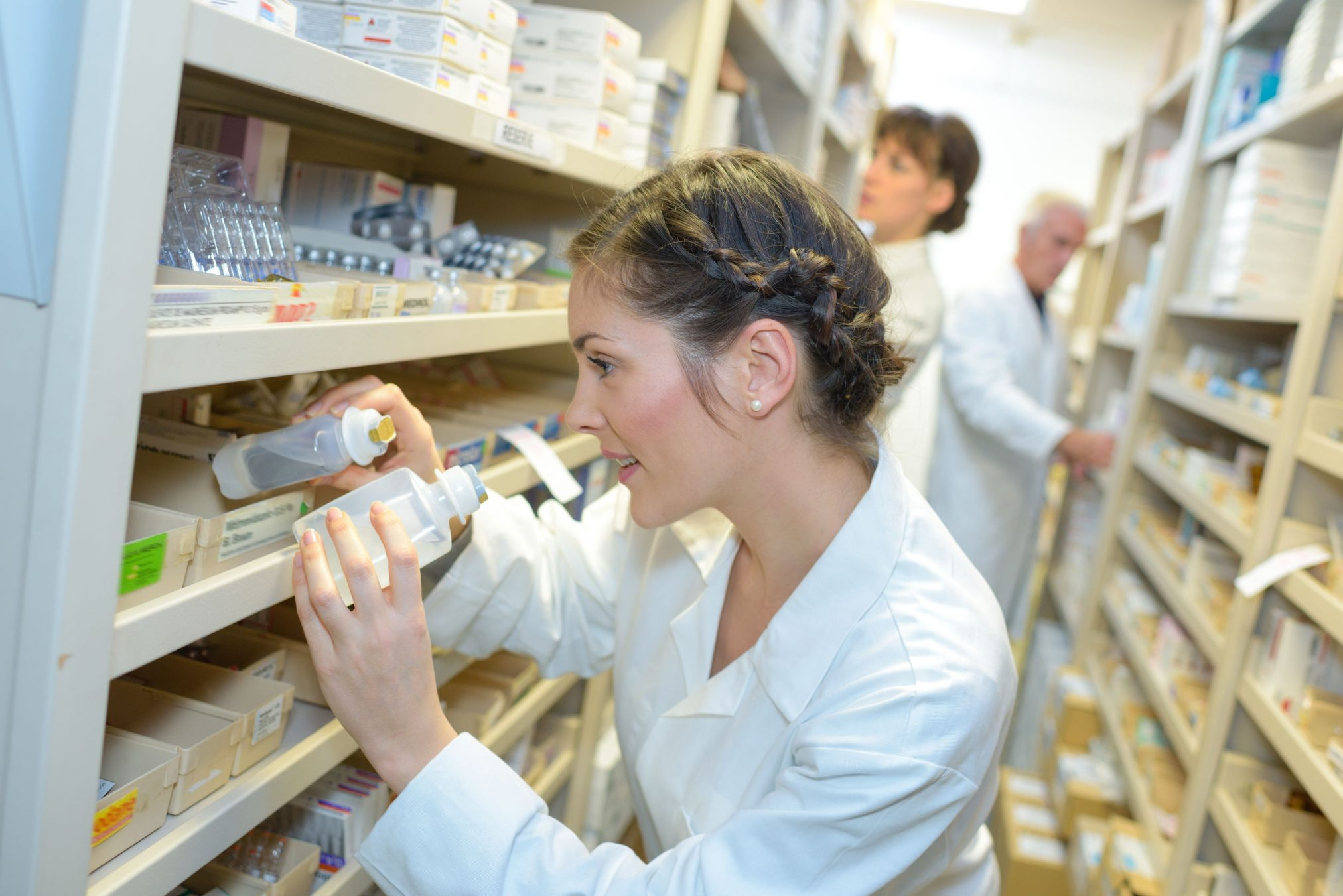 Pharmacist choosing stock from shelves