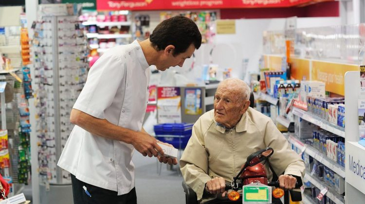 pharmacist speaking to elderly man in Terry White Chemist
