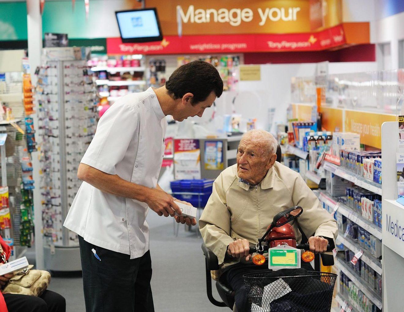 pharmacist speaking to elderly man in Terry White Chemist